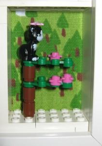 Den söta katten sitter i toppen på ett träd i skogen och spanar efter möss.